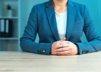 Business negotiation skills with female executive sitting at office desk with confident pose and hands crossed body language for determination and willpower